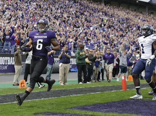 Northwestern wide receiver Tony Jones (6) scores a touchdown as Maine defensive back Axel Ofori Jr., looks on during the first quarter of an NCAA college football game in Evanston, Ill., Saturday, Sept. 21, 2013. (AP Photo/Nam Y. Huh)