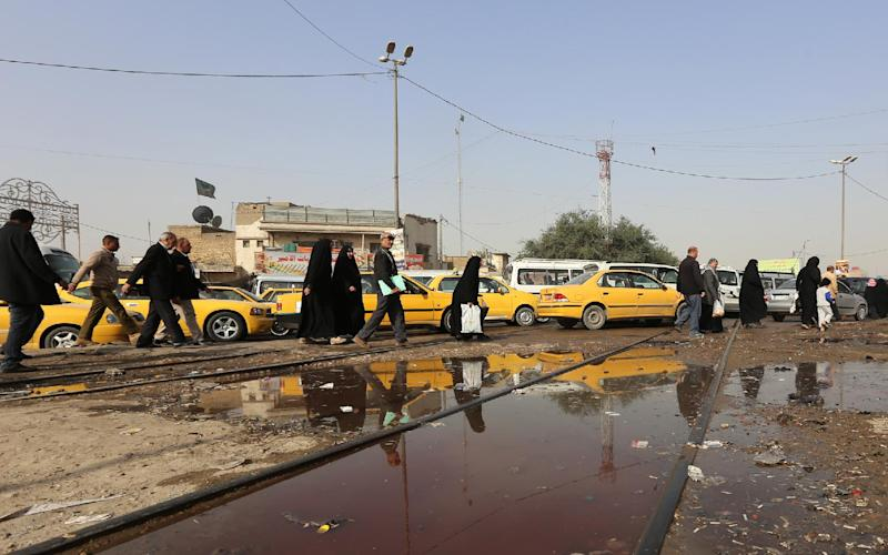 Iraqis walk past a pool of blood in the aftermath of a suicide bomb attack in the Shiite-majority district of Kadhimiyah, north Baghdad, on February 9, 2015 (AFP Photo/Sabah Arar)