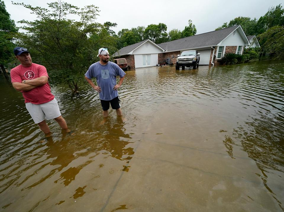Danny Gonzales, right, stands in front of his flooded house with his neighbor Bob Neal, upset with power company trucks driving though the flooded neighborhood pushing water back into his home, after Tropical Storm Claudette passed through, in Slidell, Louisiana (AP)