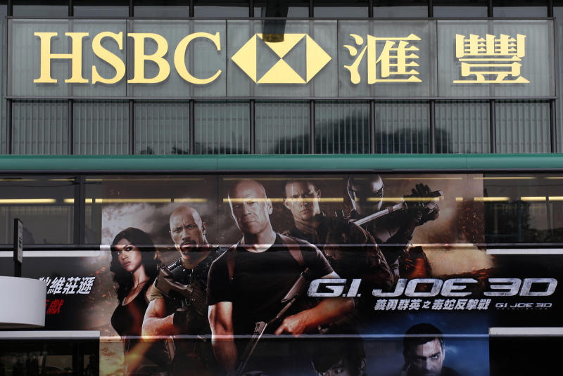 A bus featuring a hollywood movie advertisement drives past the HSBC's Hong Kong headquarters in central district of Hong Kong Monday, March 4, 2013. The HSBC banking group said Monday its net profit dropped 17 percent in 2012, when it had to pay a hefty U.S. fine to settle money-laundering claims. But earnings remained robust at US$13.5 billion as Asian businesses performed well. (AP Photo/Vincent Yu)