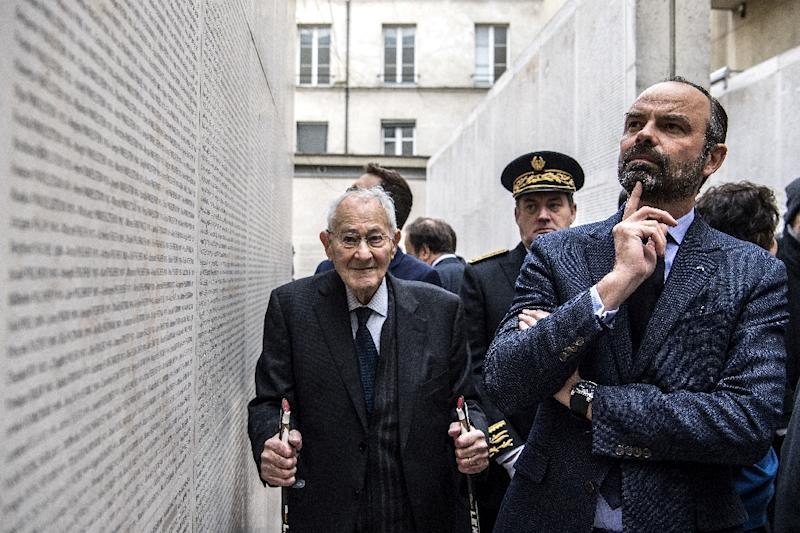 French Prime Minister Edouard Philippe (right)  reads names on the 'Wall of Names' during a visit to the Shoah Memorial Museum in Paris where a new exhibition showcases art looted by the Nazis