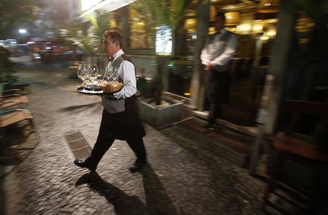 Waiter Luis Rodrigues carries food to customers at the Don Camillo restaurant before he and fellow waiters play their regular Monday night soccer match in Rio de Janeiro October 15, 2013. Waiters by day, the soccer enthusiasts who call their team Don Fogo, or Mr. Fire, play at the Aterro do Flamengo soccer field south of Rio every Monday night after closing up at 1:30 am. They are just a few of many Brazilians who share the soccer passion that is growing as the 2014 World Cup, hosted by Brazil, approaches. Picture taken October 15, 2013. REUTERS/Sergio Moraes (BRAZIL - Tags: SPORT SOCCER SOCIETY)