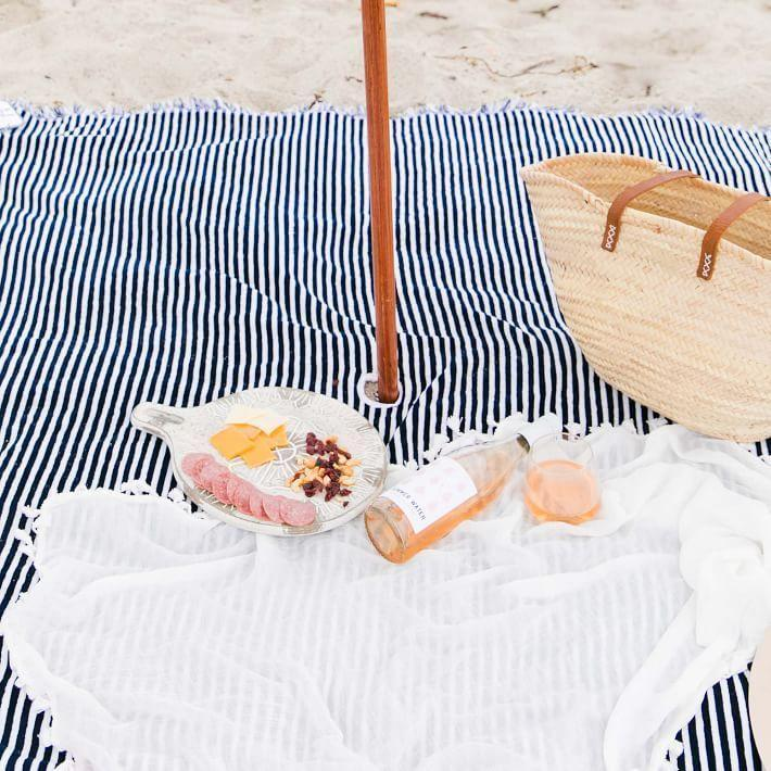 """<p><strong> West Elm</strong></p><p>westelm.com</p><p><strong>$99.00</strong></p><p><a href=""""https://go.redirectingat.com?id=74968X1596630&url=https%3A%2F%2Fwww.westelm.com%2Fproducts%2Flcl-business-pleasure-co-the-beach-blanket-d10960%2F&sref=https%3A%2F%2Fwww.goodhousekeeping.com%2Fhome-products%2Fg36111135%2Fbest-picnic-blankets%2F"""" rel=""""nofollow noopener"""" target=""""_blank"""" data-ylk=""""slk:Shop Now"""" class=""""link rapid-noclick-resp"""">Shop Now</a></p><p>This extra-large cotton blanket with a leather strap doesn't disappoint. </p>"""