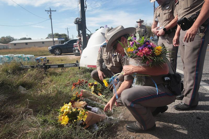 Police move flowers placed at a barricade near the First Baptist Church of Sutherland Springs on Monday. Gunman Devin Patrick Kelley killed 26 people and wounded 20 others when he opened fire during a Sunday service at the Texas church.