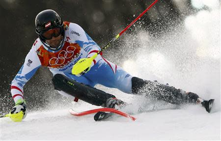 Austria's Mario Matt clears a gate during the first run of the men's alpine skiing slalom event at the 2014 Sochi Winter Olympics at the Rosa Khutor Alpine Center February 22, 2014. REUTERS/Ruben Sprich