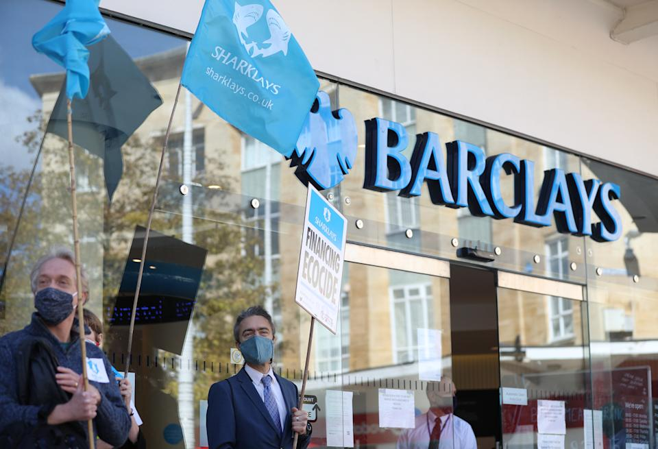 Banners held up by protesters outside Barclays bank in Broadmead, Bristol, to protest against what they have termed the financing of climate devastation by the bank. Extinction Rebellion and Stop Ecocide created a mock crime scene outside the branch as part of the protest.