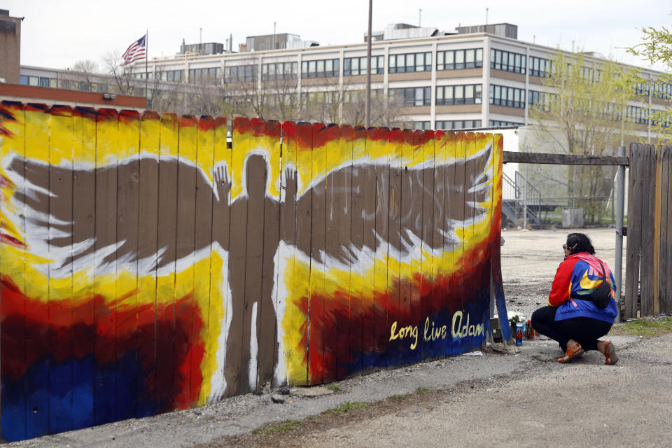 Andrea Fernanda Serrano kneels as she pays her respect to the site where 13-year-old Adam Toledo. was shot by police now marked with a mural in the Little Village neighborhood of Chicago, Friday, April 16, 2021, a day after the body camera video release of fatal police shooting of 13-year-old Adam Toledo. (AP Photo/Shafkat Anowar)