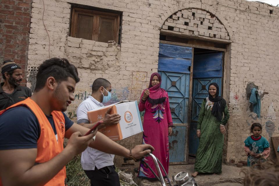 Non-governmental organization Resala Nour Ala Nour workers distribute cartons filled with food to people who have been greatly affected by the coronavirus outbreak, in Cairo, Egypt, Thursday, April 9, 2020. (AP Photo/Nariman El-Mofty)