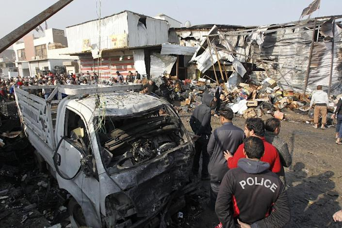 Iraqis inspect the site of an attack at Baghdad's main vegetable market on January 8, 2017 (AFP Photo/Sabah Arar)