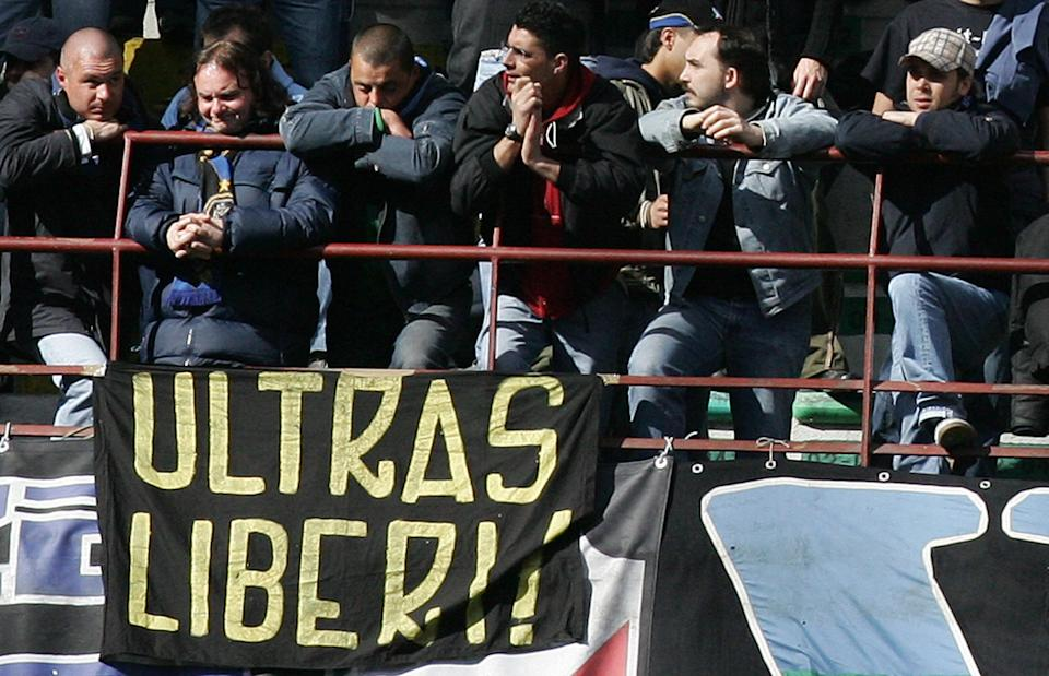 """MILAN, Italy:  Inter Milan's fans sit by a flag reading """"Ultra Free"""" during the serie A football match Inter Milan-Cagliari at San Siro stadium in Milan, 17 April 2005. European football's governing body UEFA handed Inter Milan a six-match stadium ban on Friday after their quarter-final with AC Milan was abandoned when Inter fans threw flares on to the pitch. AFP PHOTO / Paco SERINELLI  (Photo credit should read PACO SERINELLI/AFP/Getty Images)"""
