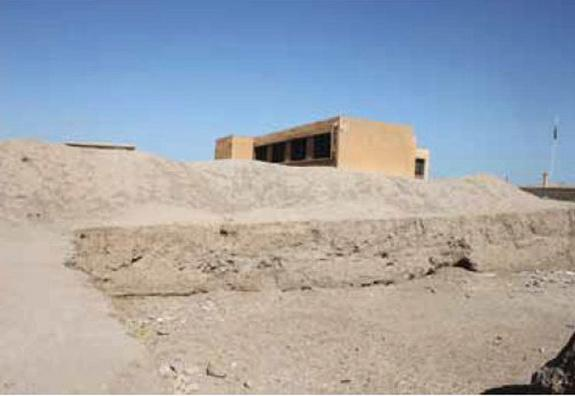 A bulldozer cut into part of the ancient city of Hamoukar by contractors building an addition to a school. Without protection at the site, modern-day buildings are being erected over it. Shot taken in April 2012.