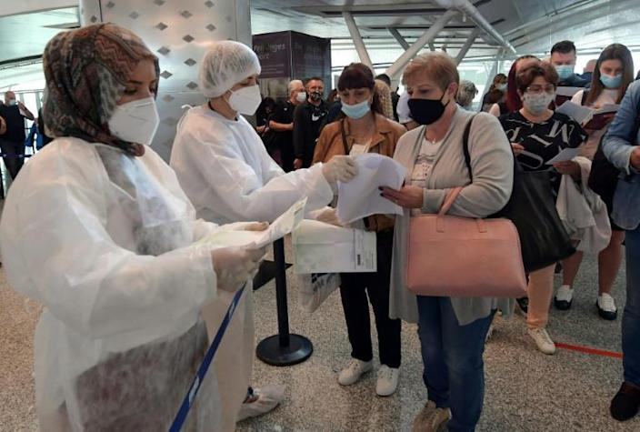 Tunisian health workers check the Covid-19 documentation of European tourists upon their arrival at Enfidha-Hammamet International Airport near the Mediterranean resort town of Sousse