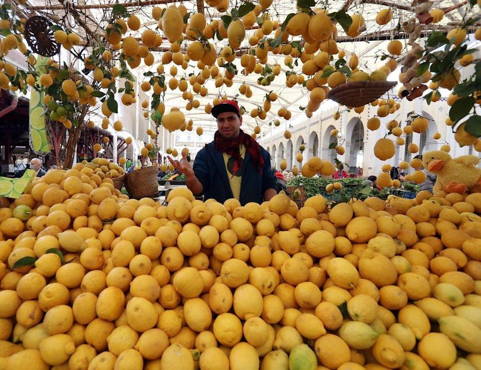 A man poses behind a stall full of lemons.