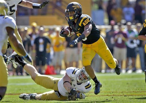 Arizona State running back D.J. Foster (8) escapes the reach of UCLA Bruins defensive tackle Ellis McCarthy during the first half of an NCAA college football game, Saturday, Oct. 27, 2012, in Tempe, Ariz. (AP Photo/Matt York)
