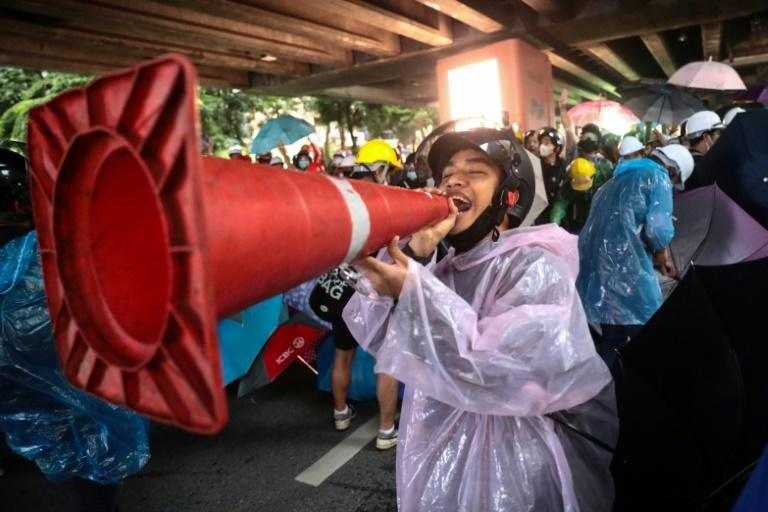 A Thai protester jokingly uses a traffic cone as a loudhailer during a rally at Victory Monument in Bangkok. The protestors are calling for the resignation of the prime minister and reforms to the monarchy