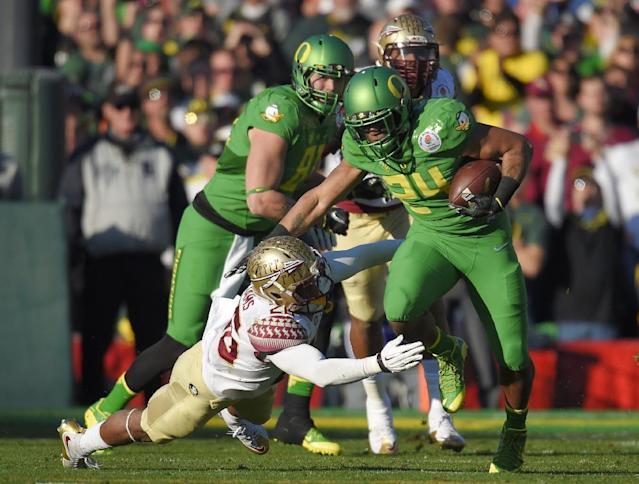 Oregon running back Thomas Tyner, front right, runs past Florida State defensive back P.J. Williams during the first half of the Rose Bowl NCAA college football playoff semifinal, Thursday, Jan. 1, 2015, in Pasadena, Calif. (AP Photo/Mark J. Terrill)