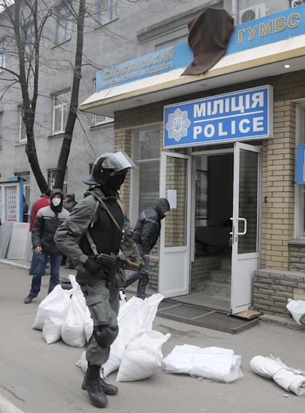 Armed pro-Russian activists occupy the police station carrying riot shields in the eastern Ukraine town of Slovyansk on Saturday, April 12, 2014. Pro-Moscow protesters have seized a number of government buildings in the east over the past week, undermining the authority of the interim government in the capital, Kiev. (AP Photo/Efrem Lukatsky)