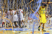 FILE - In this April 8, 2013, file photo, Michigan guard Trey Burke (3) walks off the court as confetti falls on Louisville players, including Russ Smith (2), Luke Hancock (11), Stephan Van Treese (44) and Zach Price (25), after the NCAA Final Four tournament college basketball championship game in Atlanta. The Final Four teams would've been in Atlanta, Friday, April 3, 2020, getting in their final practices for Saturday's semifinal games. (Curtis Compton/Atlanta Journal-Constitution via AP, File)