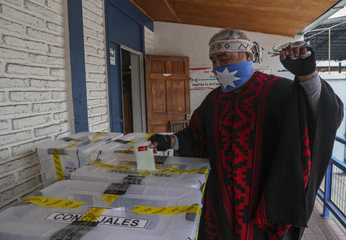 A Mapuche Indigenous man known as Clay casts his ballot at a polling station during the second day of the Constitutional Convention election to select assembly members that will draft a new constitution, in Santiago, Chile, Sunday, May 16, 2021. The face of a new Chile begins taking shape this weekend as the South American country elects 155 people to draft a constitution to replace one that has governed it since being imposed during a military dictatorship. (AP Photo/Esteban Felix)