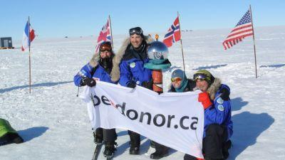 The Test Your Limits team marks their achievement at the South Pole with their official banner.
