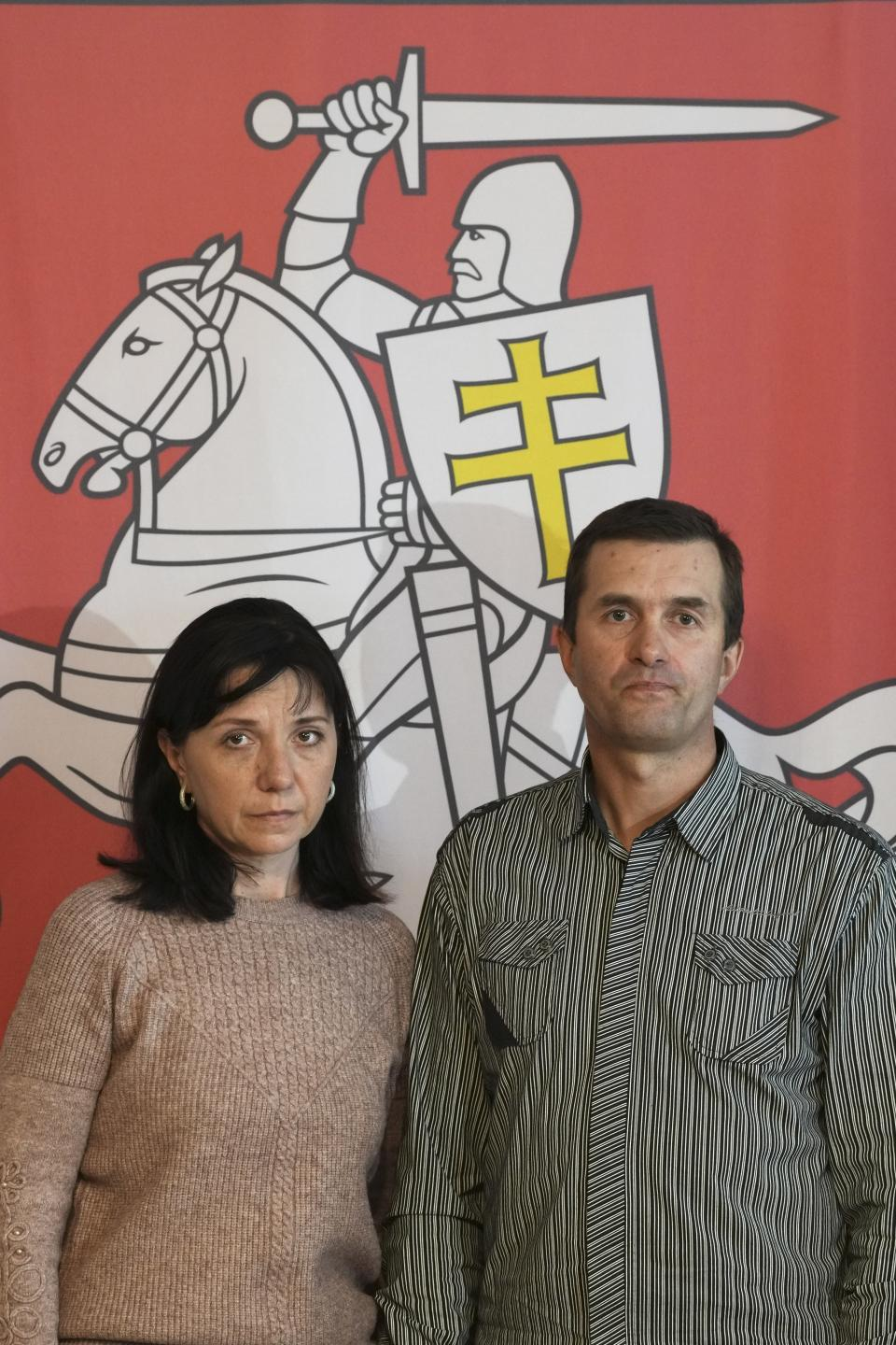 """FILE - In this May 27, 2021, file photo, Natalia Pratasevich, left, and Dzmitry Pratasevich, the parents of dissident journalist Raman Pratasevich, pose in front of an old Belarusian national emblem after a news conference in Warsaw, Poland. The journalist was arrested in Minsk on Sunday, May 23, 2021, after Belarusian flight controllers told a Ryanair jetliner he was on to land in Minsk, citing a bomb threat. """"I am begging you, help me free my son!"""" said Natalia Pratasevich. (AP Photo/Czarek Sokolowski, File)"""