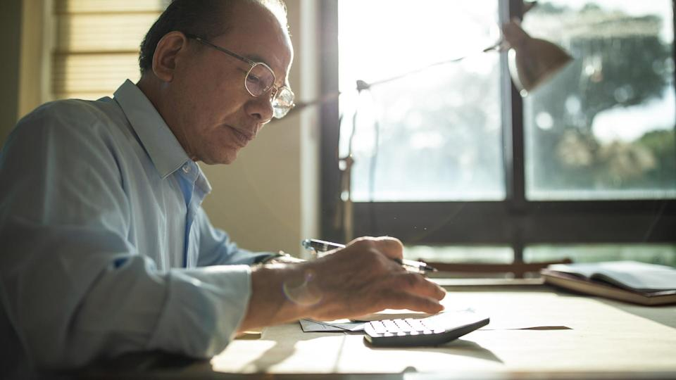 Senior Taiwanese man with eyeglasses sitting in dining room at home and calculating bills for paying.