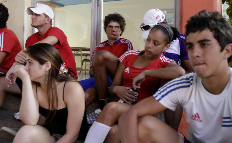 In this Jan. 26, 2012 photo, Damian Lopez, center, who was injured as a teenager by a high-voltage electrical wire when untangling a kite, sits with other athletes after training at the Reinaldo Paseiro velodrome in Havana, Cuba.  The accident cost him both his forearms, melted much of the skin from his face and left him in a coma from which doctors predicted he would never emerge. Twenty-two years later, Lopez, 35, is close to realizing an unlikely dream by representing Cuba at the 2012 London Paralympics in cycling, the sport that he says kept him from drowning in self-pity and despair.  (AP Photo/Franklin Reyes)