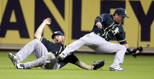 Oakland Athletics second baseman Nick Punto, right, trips over right fielder Brandon Moss as he catches a pop fly hit by Houston Astros' Robbie Grossman to end the ninth inning of a baseball game Tuesday, July 29, 2014, in Houston. The Athletics beat the Astros 7-4. (AP Photo/David J. Phillip)