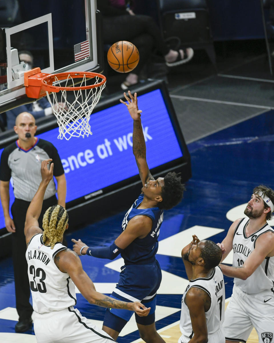 Minnesota Timberwolves forward Jaden McDaniels, second from left, goes up for a shot as Brooklyn Nets forward Nicolas Claxton, left, Nets forward Kevin Durant, second from right, and Nets forward Joe Harris look on during the first half of an NBA basketball game Tuesday, April 13, 2021, in Minneapolis. (AP Photo/Craig Lassig)
