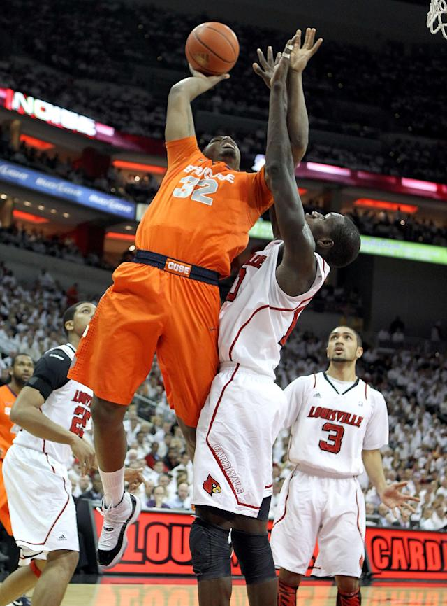 LOUISVILLE, KY - FEBRUARY 13: Kris Joseph #32 of the Syracuse Orange shoots the ball while defended by Gorgui Dieng #10 of the Louisville Cardinals during the Big East Conference game at KFC YUM! Center on February 13, 2012 in Louisville, Kentucky. (Photo by Andy Lyons/Getty Images)