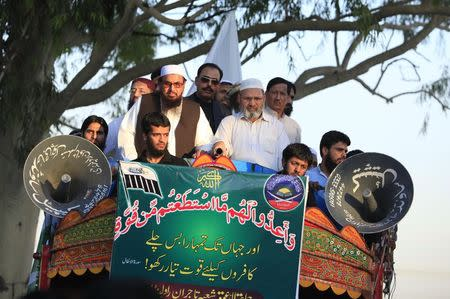 Hafiz Saeed, head of the Jamaat-ud-Dawa organisation and founder of Lashkar-e-Taiba, stand on a truck with others during a rally to mark the 16th anniversary of Pakistan's first successful nuclear test in 1998, in Islamabad May 28, 2014. REUTERS/Faisal Mahmood