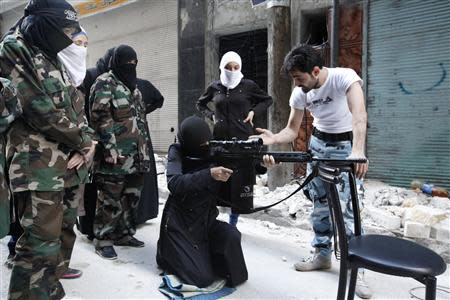 "A female member of the ""Mother Aisha"" battalion receives instruction as she holds a rifle during military training in Aleppo's Salaheddine district, September 19, 2013. REUTERS/Loubna Mrie"