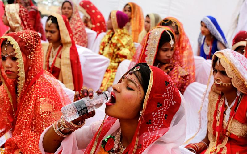 An Indian bride drinks water as she sits with other brides during a mass marriage ceremony - Credit: SANJEEV GUPTA / EPA