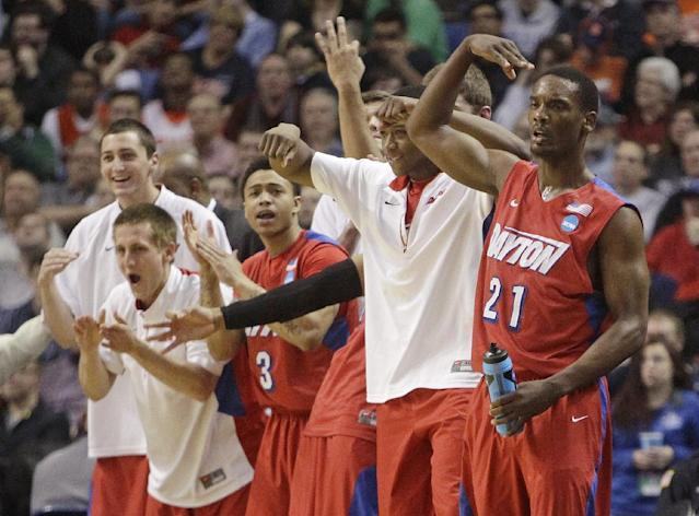 Dayton's Dyshawn Pierre (21) celebrates with teammates during the second half of a third-round game against Syracuse in the NCAA men's college basketball tournament in Buffalo, N.Y., Saturday, March 22, 2014. (AP Photo/Bill Wippert)