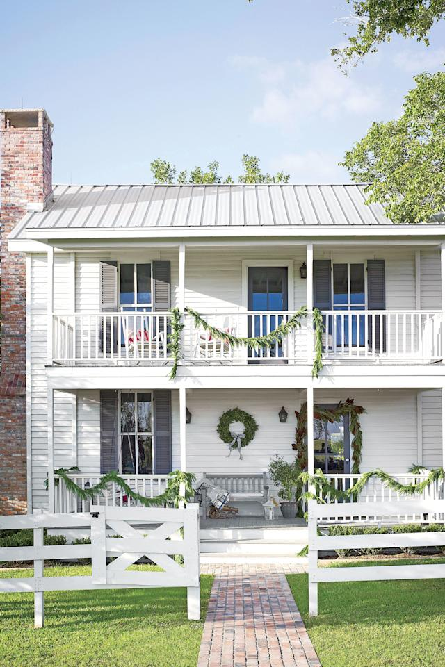 <p>An old, bright-white clapboard farmhouse doesn't need much to look absolutely charming. Wispy pine garland pops on the monochromatic exterior. </p>