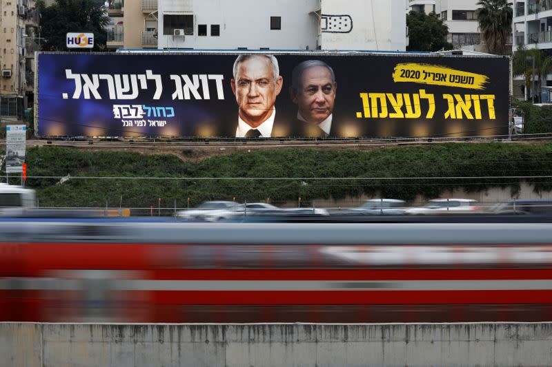 FILE PHOTO: Traffic moves past a Blue and White party election campaign poster, depicting party leader Benny Gantz, and Israeli Prime Minister Benjamin Netanyahu, in Tel Aviv
