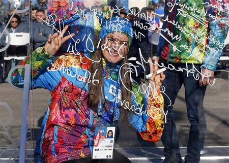 Russian pole vaulter and Mayor of the Coastal Cluster Olympic Village Isinbayeva gestures after signing the Olympic truce wall in Sochi