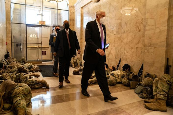 House Majority Leader Steny H. Hoyer (D-Md.) and others pass National Guard troops at rest in the U.S. Capitol.