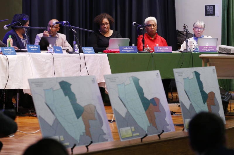 In this Dec. 16, 2019, photo, proposed redistricting maps are lined up during the Richmond School Board's last public hearing on redistricting at Ginter Park Elementary School in Richmond, Va. From New York City to Richmond, sweeping proposals to ease inequities have been scaled back or canceled after encountering a backlash. In Virginia's capital city, the school board approved a plan that reassigned some students but rejected more sweeping proposals that would have diversified Richmond's whitest elementary schools. (AP Photo/Steve Helber)