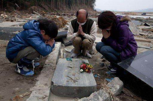 Photo taken on April 11 shows a family praying by a grave in Ishinomaki, Miyagi prefecture. A year after whole neighbourhoods full of people were killed by the Japanese tsunami, rumours of ghosts swirl in Ishinomaki as the city struggles to come to terms with the awful tragedy