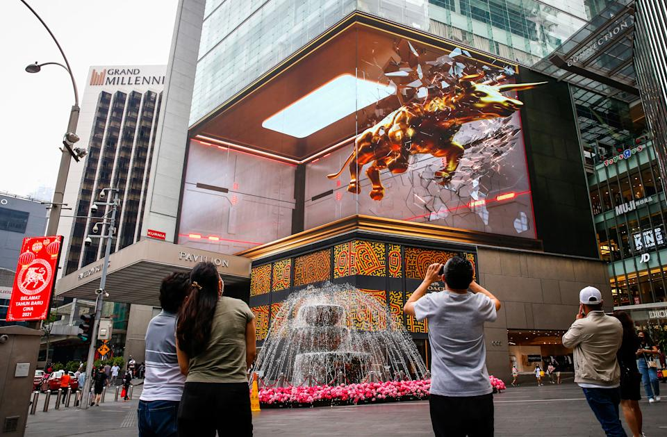 KUALA LUMPUR, MALAYSIA - 2021/02/10: People taking photos of the 3D hologram projection of the golden ox at Pavilion shopping mall. Chinese around the world will be celebrating the Chinese Lunar New Year and welcome the year of Ox which falls 12th on February. (Photo by Wong Fok Loy/SOPA Images/LightRocket via Getty Images)