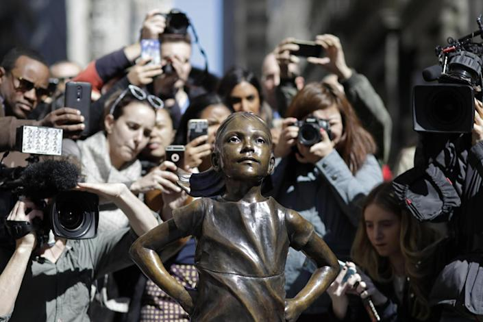 Statue of girl on Wall Street stands opposite a raging bull and is intended to highlight the challenges women face in the financial world: AP
