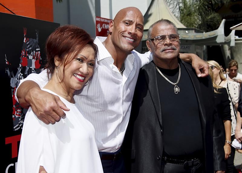 "Actor Dwayne ""The Rock"" Johnson (C) poses with his mother Ata Johnson (L) and father Rocky Johnson (R) during his hand and footprints ceremony in the forecourt of the TCL Chinese Theatre in celebration of his new movie ""San Andreas,"" in Hollywood, California May 19, 2015. REUTERS/Danny Moloshok"
