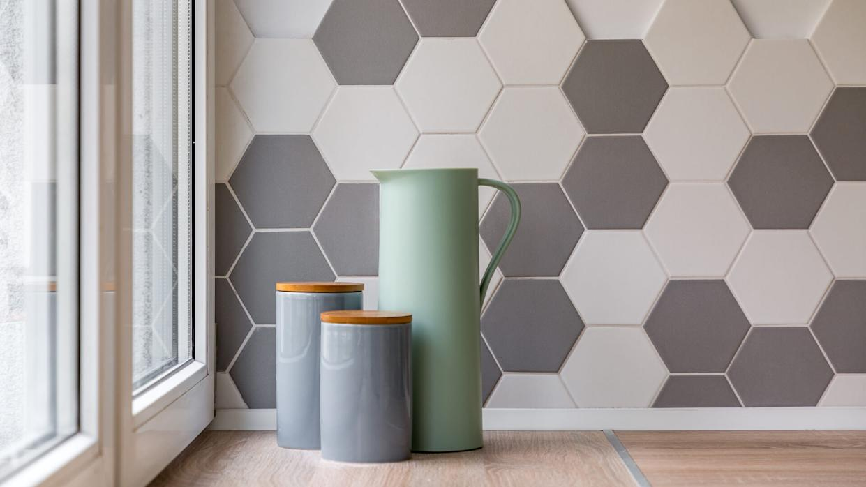 Close-up of ceramic containers, jug and hexagon tiles in kitchen.