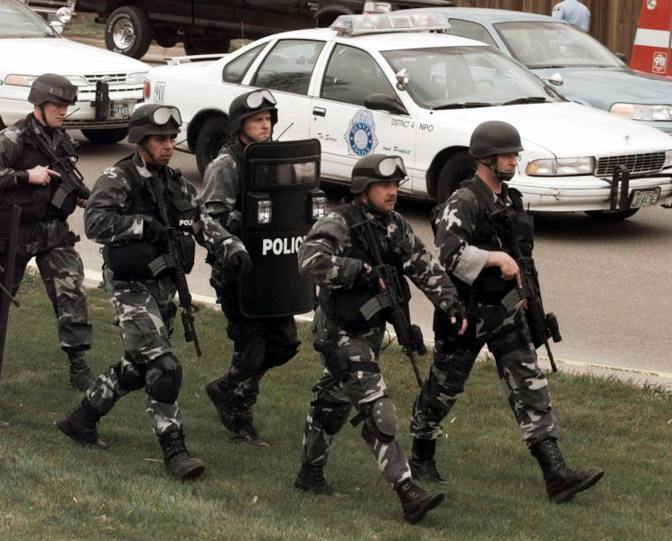 FILE - In this April 20, 1999, file photo, members of a police SWAT team march to Columbine High School in Littleton, Colo., as they prepare to do a final search of the school after two gunmen opened fire on campus. The shooting shocked the country as it played out on TV news shows from coast to coast. (AP Photo/Ed Andrieski, File)