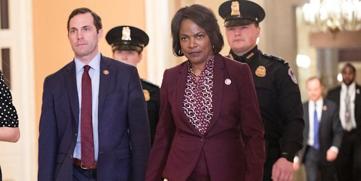 Representatives Jason Crow (D-CO) (left) and Val Demings (D-FL) (right), two of the Democratic impeachment managers from the House of Representatives, head back to the Senate floor during the Senate impeachment trial of President Donald Trump on January 27, 2020 in Washington, DC.