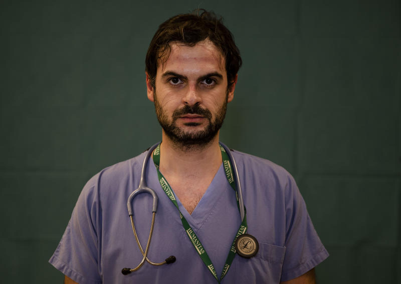 Alessandro D'Aveni, 33, an oncologist working in the COVID sub-intensive care unit at the Humanitas Gavazzeni Hospital in Bergamo, Italy poses for a portrait at the end of his shift Friday, March 27, 2020. (AP Photo/Antonio Calanni)