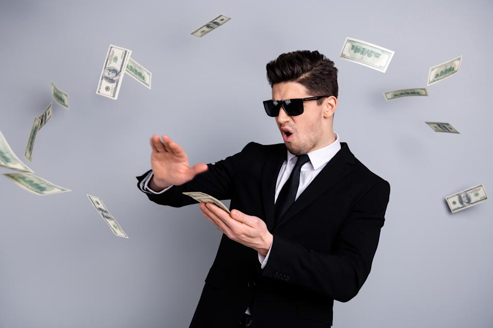 Man in a suit wearing sunglasses. He is throwing money.