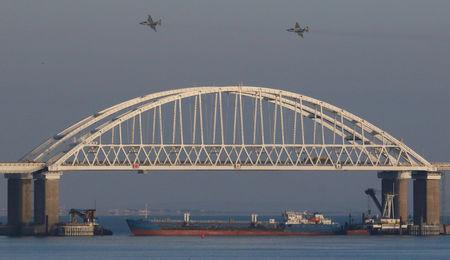 Russian jet fighters fly over a bridge connecting the Russian mainland with the Crimean Peninsula with a cargo ship beneath it after three Ukrainian navy vessels were stopped by Russia from entering the Sea of Azov via the Kerch Strait in the Black Sea, Crimea November 25, 2018. REUTERS/Pavel Rebrov