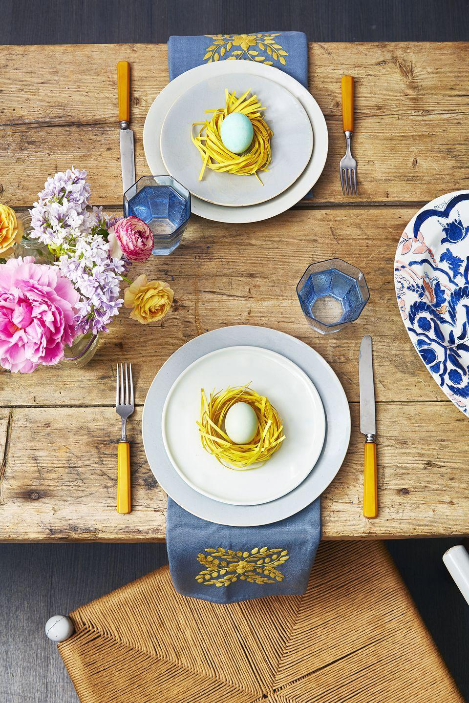 <p>Create a spring-inspired table setting by making faux-grass nests and placing decorated eggs inside. A bright bouquet completes the look. </p>